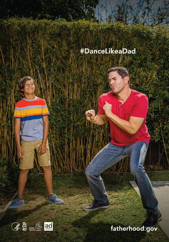 Dad dancing in backyard, son watching and laughing